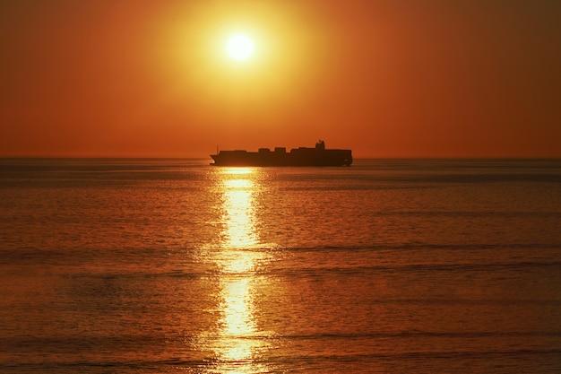 Um grande navio no horizonte no oceano atlântico sob o sol brilhante e o pôr do sol vermelho. reflexo da luz solar na água