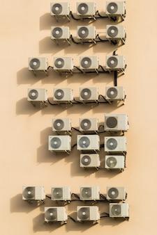 Um grande número de aparelhos de ar condicionado na parede marrom