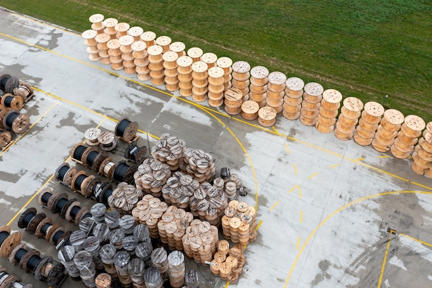 Um grande número de bobinas de madeira com tubos de polipropileno. produção e armazenamento de tubos de polipropileno para comunicações urbanas. vista de cima