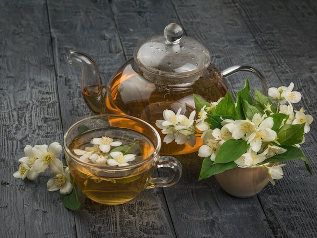 Um grande número de flores de jasmim e um bule de vidro com chá de flores sobre uma mesa de madeira.