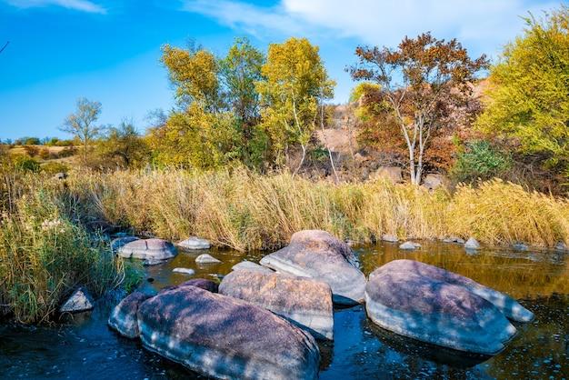 Um grande número de minerais de pedra cobertos por vegetação verde acima de um pequeno rio na pitoresca ucrânia e sua bela natureza