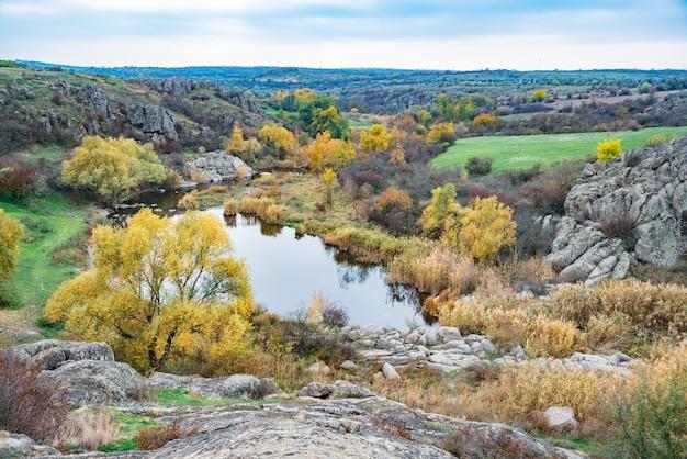 Um grande número de minerais de pedra cobertos por vegetação verde situada acima de um pequeno rio