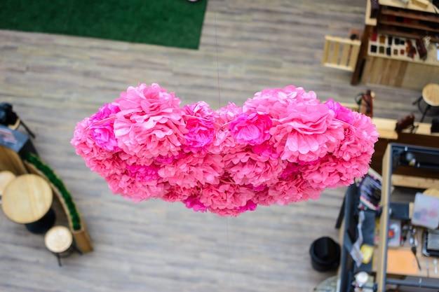 Um grande origami em forma de coração rosa, colhido de muitas flores. decoração de papel grande pendurada em uma corda.