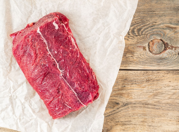 Um grande pedaço de carne crua. lombinho de carne em papel pergaminho branco sobre backgr rústico áspero