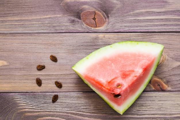 Um grande pedaço de sementes de melancia e melancia em um fundo de madeira.