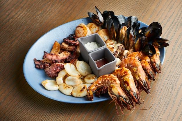 Um grande prato de frutos do mar fritos - lulas, polvos, mexilhões, vieiras, camarão. frutos do mar sortidos em uma placa de cerâmica em uma superfície de madeira. efeito de filme durante a postagem. foco suave