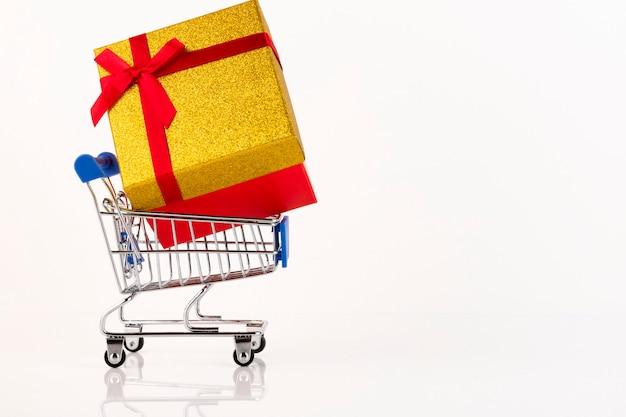 Um grande presente com uma fita de presente na cesta de um comprador em um fundo branco. copie o espaço