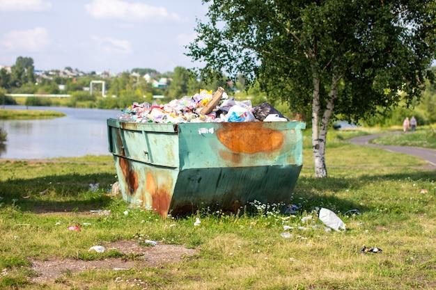 Um grande recipiente de metal, verde e enferrujado para lixo e lixo doméstico