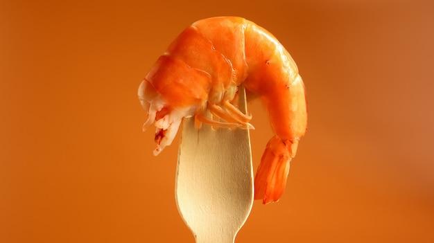 Um grande rei cozido camarão na pia em um garfo de madeira sobre um fundo marrom. infraestrutura de crustáceos do decápode, comendo carniça. delicadeza do mar. o camarão é usado na culinária. petisco de cerveja.