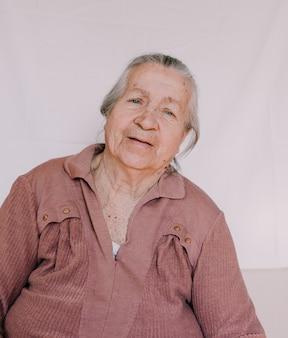 Um grande retrato de uma avó com rugas profundas e manchas de idade no rosto.