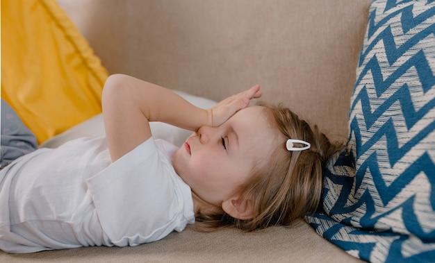 Um grande retrato de uma menina com sono deitada no sofá com a mão esfregando os olhos depois de dormir. despertar em crianças