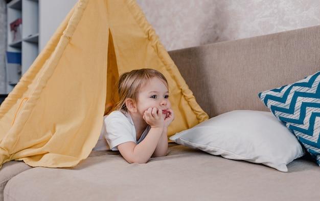 Um grande retrato de uma menina deitada dentro de uma tenda amarela. o rosto triste de uma criança