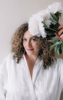 Um grande retrato de uma mulher em um vestido branco com cabelos cacheados, segurando um buquê de peônias brancas na mão.