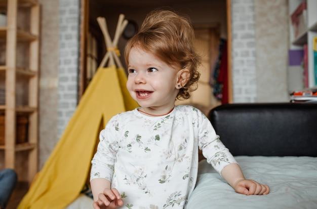 Um grande retrato de uma pequena menina rindo em uma sala. bebê feliz
