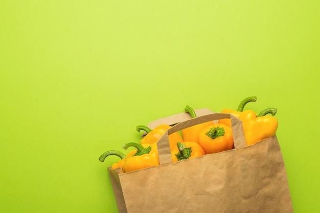 Um grande saco de papel com pimentão em um fundo verde. comida vegetariana.