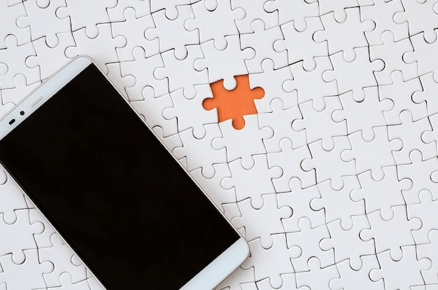 Um grande smartphone moderno com uma tela de toque encontra-se em um quebra-cabeça branco