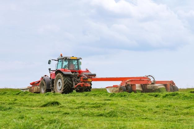Um grande trator vermelho com dois cortadores corta a grama verde em um silo.