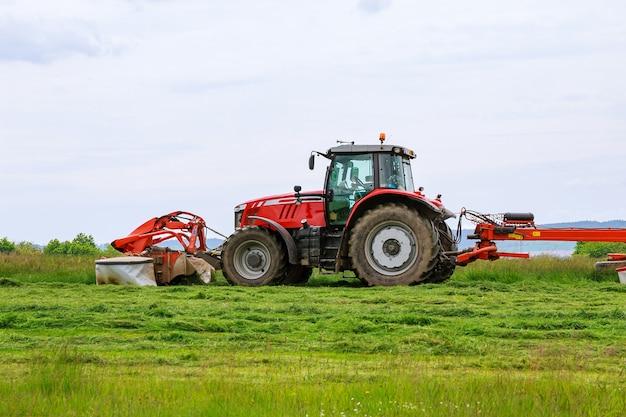 Um grande trator vermelho corta a grama para ensilagem no campo