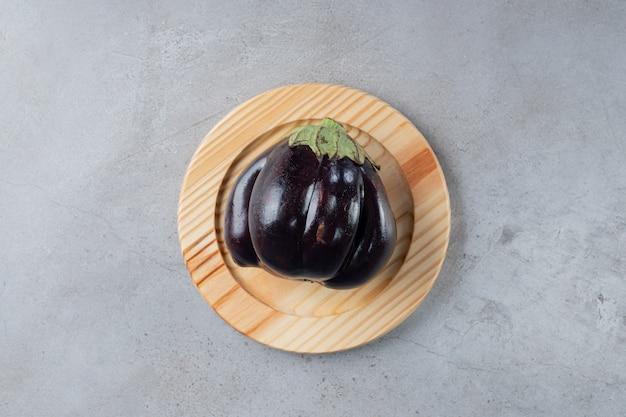 Um grande vegetal de berinjela roxa em uma placa de madeira. foto de alta qualidade