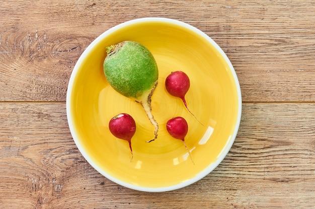 Um grande verde e três pequenos rabanetes vermelhos como se estivessem se movendo em um prato amarelo
