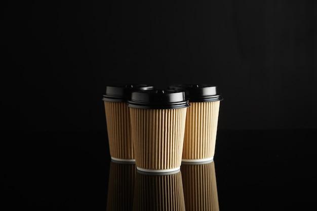 Um grupo de 3 xícaras de café descartáveis idênticas de papelão ondulado marrom claro com tampas pretas no meio de uma mesa refletida preta com parede preta atrás.