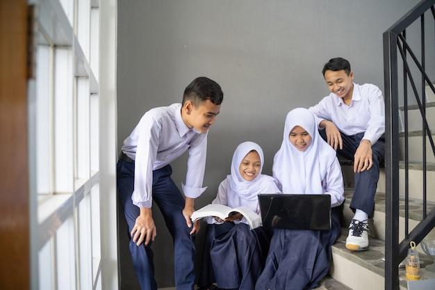 Um grupo de adolescentes asiáticos em uniformes do ensino fundamental estuda juntos usando um laptop e um livro