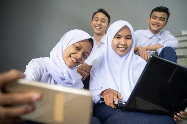 Um grupo de adolescentes em uniformes escolares tirando selfies com um celular enquanto usam um laptop
