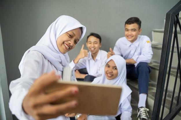 Um grupo de adolescentes em uniformes escolares tirando selfies junto com um celular