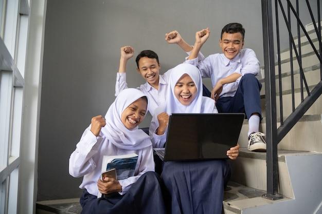 Um grupo de adolescentes empolgados em uniformes escolares usando um laptop em conjunto com movimentos de punhos cerrados ...