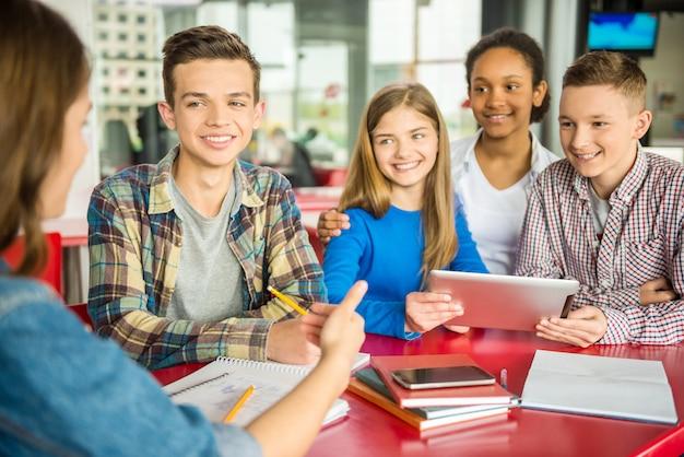 Um grupo de adolescentes sentados à mesa no café.