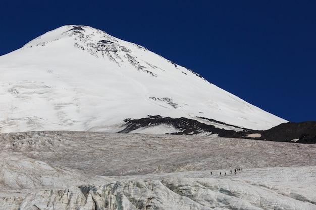 Um grupo de alpinistas na geleira contra o pico oriental do monte elbrus, no cáucaso do norte, na rússia.