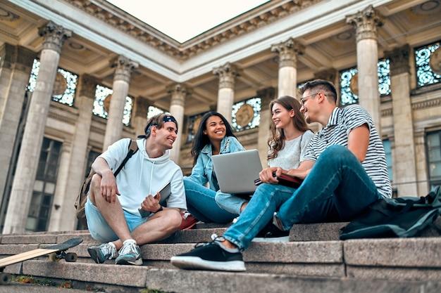 Um grupo de alunos com laptops senta nas escadas perto do campus e se comunica.