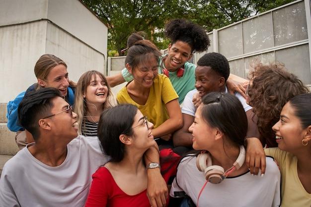 Um grupo de alunos se divertindo fora de felizes colegas de classe na escola de volta à escola juntos a ...