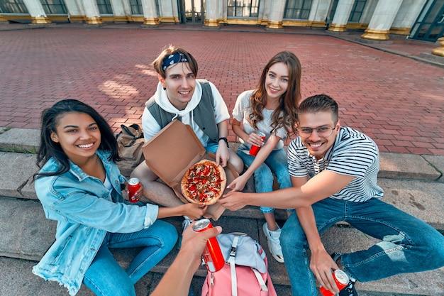 Um grupo de alunos senta-se na escada fora do campus e come pizza com refrigerante