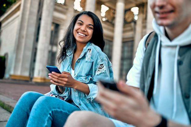 Um grupo de alunos senta-se nas escadas fora do campus e usa seus smartphones.