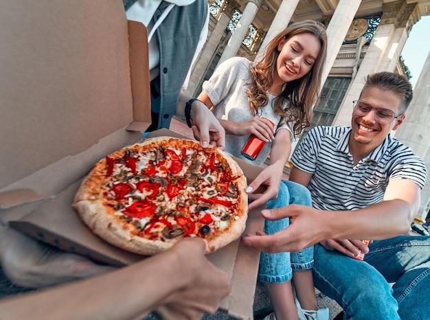 Um grupo de alunos senta-se nos degraus fora do campus e come pizza com refrigerante. um grupo de amigos está relaxando e conversando.