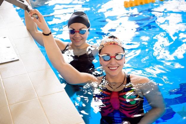 Um grupo de amigas na piscina de esportes. amigos se divertem no treinamento