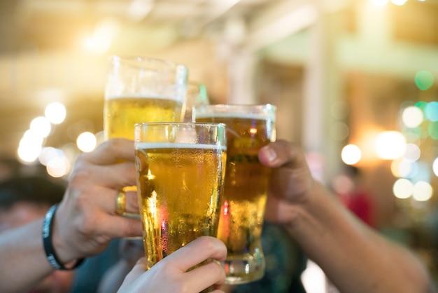Um grupo de amigos com bebidas em uma boate. os jovens estão desfrutando