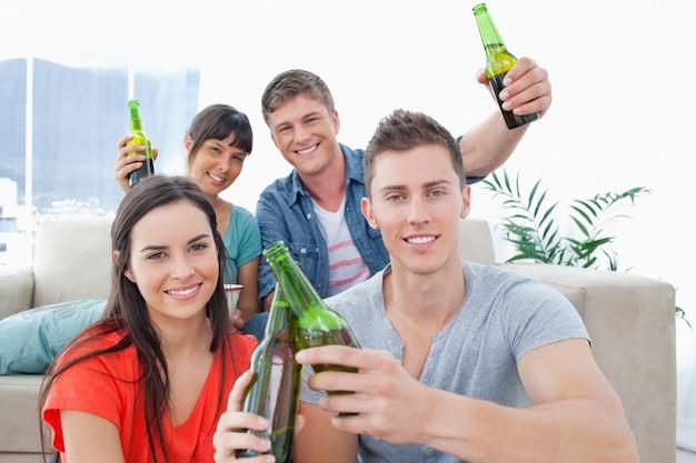 Um grupo de amigos comemorando juntos garrafas