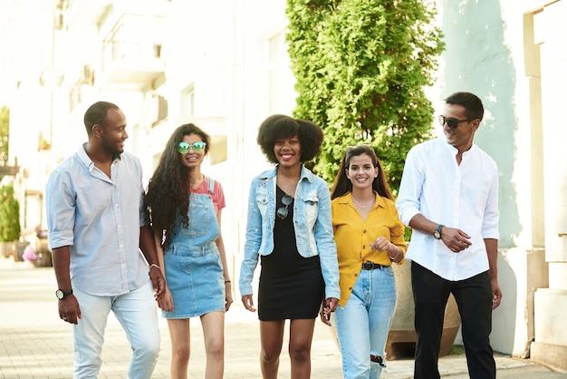 Um grupo de amigos de diferentes nacionalidades caminha pela cidade e olha para a câmera.