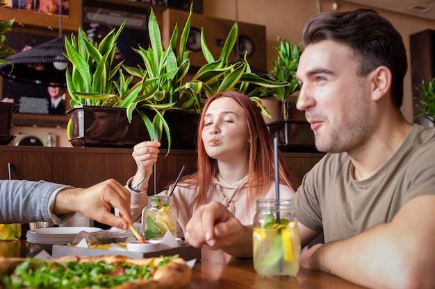 Um grupo de amigos descansando em um bar. comendo, bebendo, comida na mesa. amizade