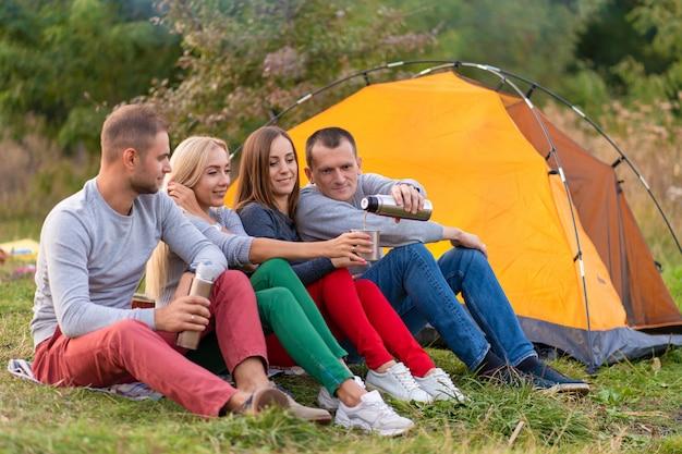 Um grupo de amigos está desfrutando de uma bebida quente de uma garrafa térmica