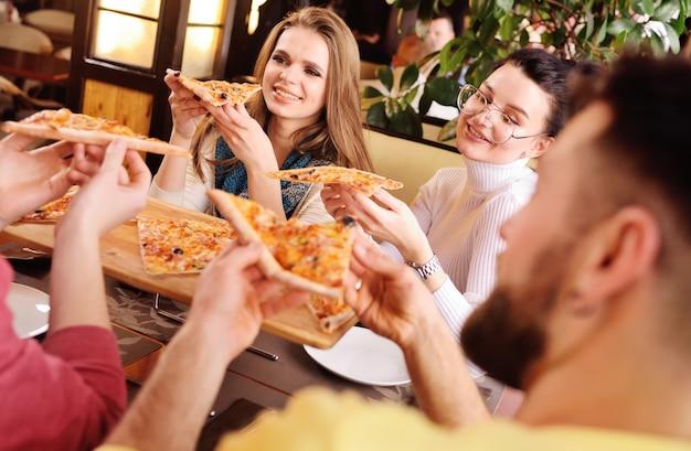 Um grupo de amigos fala e sorri em um café e come a pizza.