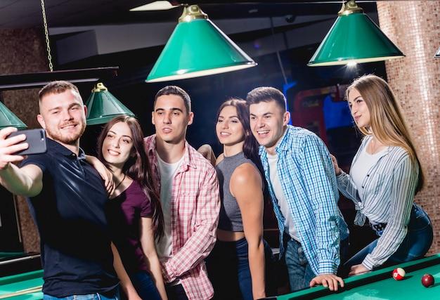 Um grupo de amigos faz uma selfie na mesa de bilhar. posando com uma sugestão em suas mãos.