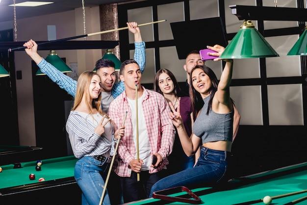 Um grupo de amigos faz uma selfie na mesa de bilhar.