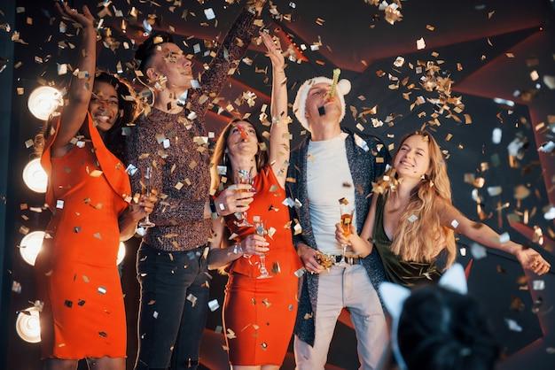 Um grupo de amigos posando e se divertindo com bonecos de neve e champanhe. celebração de ano novo.
