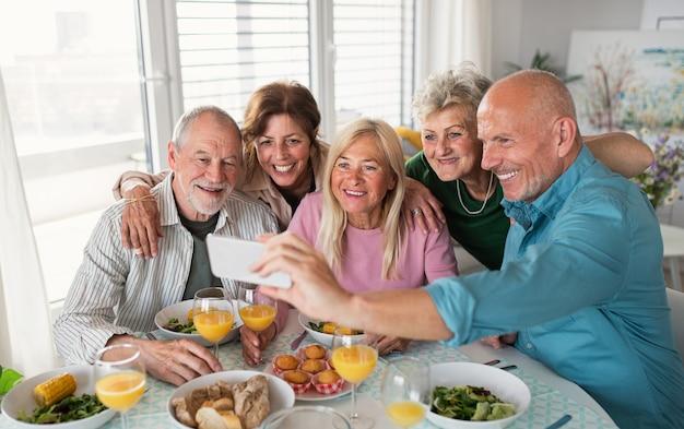 Um grupo de amigos seniores, festejando dentro de casa, tirando selfie ao comer à mesa.