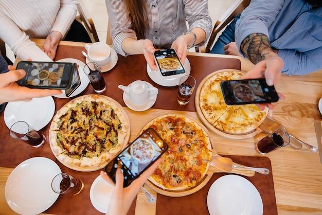 Um grupo de amigos tira uma foto em close de uma deliciosa pizza para o blog, pizzaria.