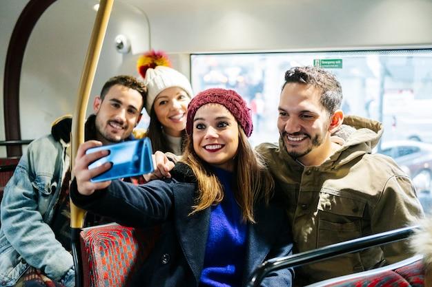 Um grupo de amigos tira uma selfie em um ônibus urbano