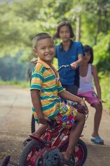 Um, grupo, de, asiático, indefinido, feliz, crianças, montando, seu, bicicleta, ligado, a, stree